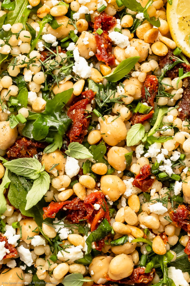 Up close overhead photo of Israeli pearl couscous tossed with sun-dried tomatoes, arugula, chickpeas and fresh herbs.