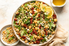 Overhead landscape photo of Israeli pearl couscous with sun-dried tomatoes, arugula and chickpeas in a large white bowl with a jar of lemon vinaigrette and ramekin of toasted pine nuts next to the bowl.