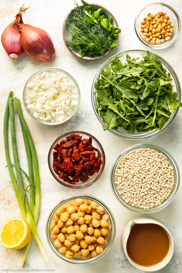 Overhead photo of all the ingredients needed to make pearl couscous neatly organized in individual bowls on a white wood surface.