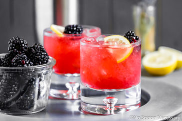 Straight on, landscap shot of a silver tray topped with two Blackberry Bramble Cocktail Recipe in a rocks glasses garnished with a blackberry and lemon slice with a small vase of flowers and cocktail shaker in the background.
