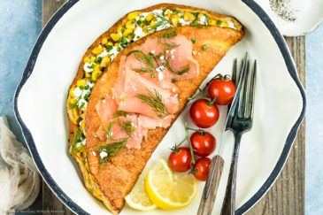 Overhead, landscape shot of a fluffy omelet filled with corn, goat cheese and chives in a white skillet with cherry tomatoes, lemon wedges and a knife and fork next to the omelet.