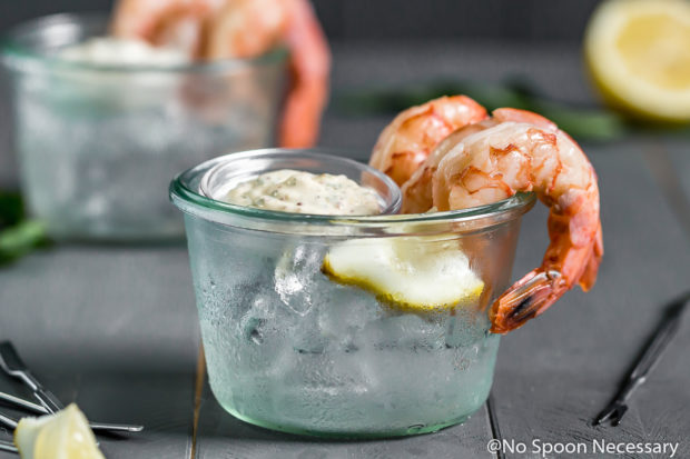 Straight on shot of a small glass bowl filled with ice with Perfect Beer Poached Shrimp Cocktail looped around the edges of the bowl and a small ramekin ofRemoulade on top of the ice; with another bowl of shrimp, shrimp forks and a lemon half blurred in the background.