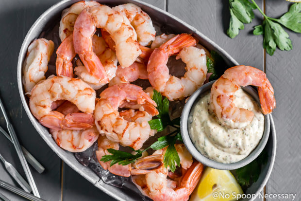 Overhead shot of a small gray tub filled with ice and topped with Perfect Beer Poached Shrimp Cocktail with Remoulade in a small ramekin with a shrimp laying on the sauce; with fresh parsley and shrimp forks on either side of the tub.