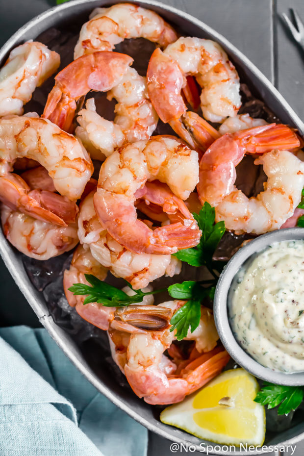 Overhead shot of a small gray tub filled with ice and topped with Perfect Beer Poached Shrimp Cocktail with Remoulade in a small ramekin; with a light blue linen and shrimp fork on either sides of the tub.