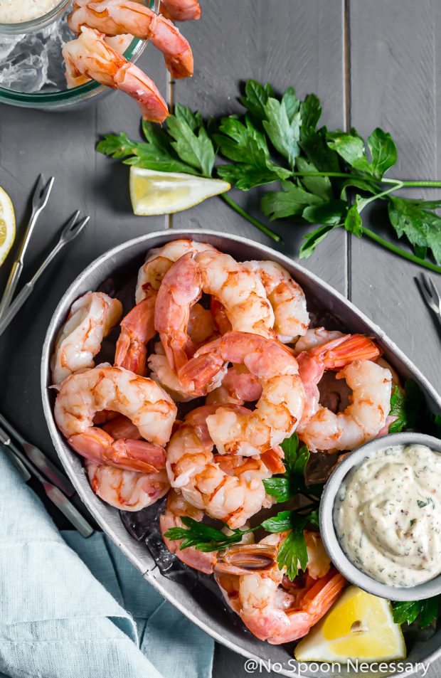 Overhead shot of a small gray tub filled with ice and topped with Perfect Beer Poached Shrimp Cocktail with Remoulade in a small ramekin; with fresh parsley, lemon wedges, another container of shrimp cocktail and a light blue linen surrounding the tub.