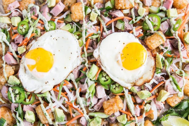 Extreme up-close, overhead shot of Banh Mi Totchos (tater tot nachos) drizzled with cilantro-lime aioli and topped with two fried eggs.