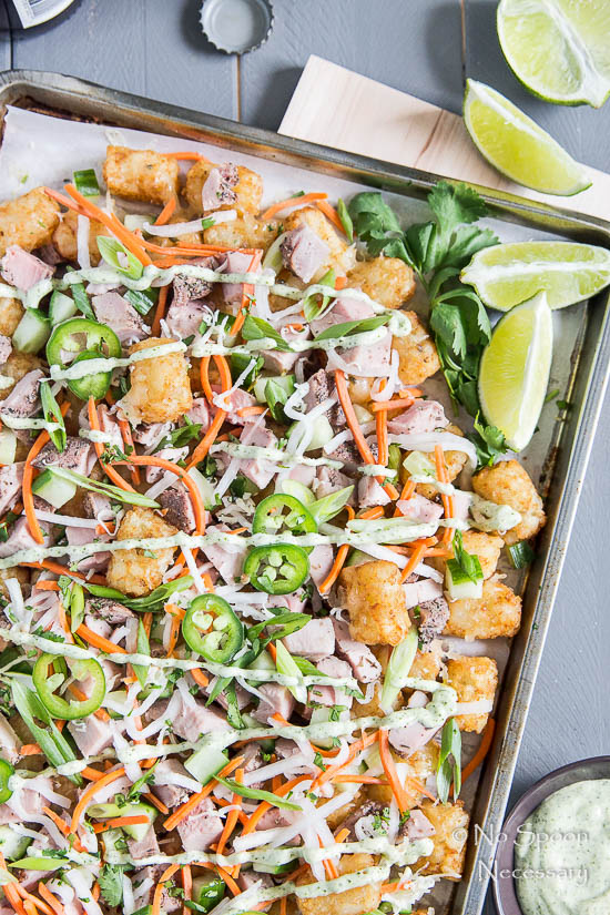Overhead, up-close shot of Banh Mi Totchos (tater tot nachos) on a sheet pan drizzled with cilantro lime aioli; with a bottle cap, lime wedges and a ramekin of aioli around the pan.
