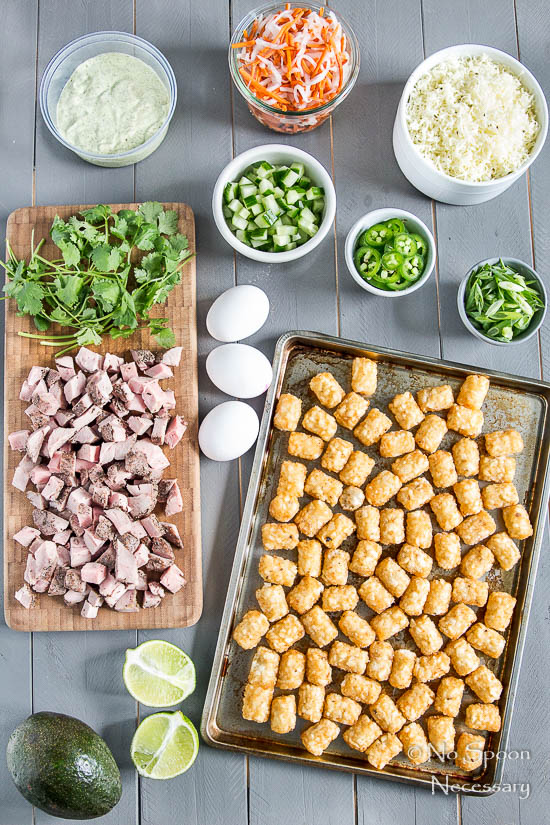 Overhead shot of all the ingredients needed to make Banh Mi Totchos (tater tot nachos) neatly organized on a gray wood board.
