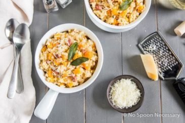 Overhead shot of a bowl of Baked Butternut Squash Risotto with Pancetta & Sage with an additional bowl of risotto, parmesan cheese, a wine glass, wine cork, linen and spoons surrounding the bowl.