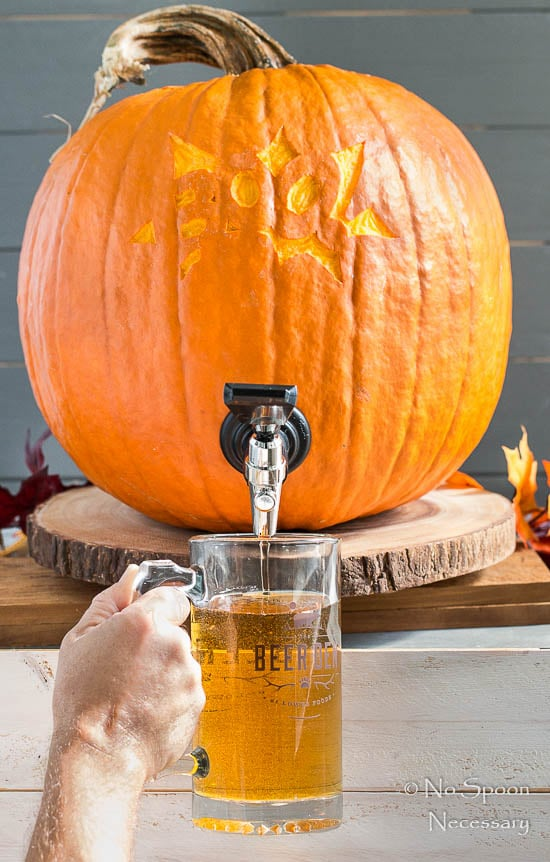 Straight on shot of a beer pouring out of a pumpkin and into a beer glass - photo of the seventh, and final step of How To Make A Pumpkin Keg.