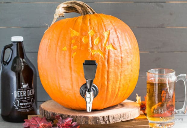 Straight on shot of a pumpkin keg with a beer growler and glass full of beer next to the keg.