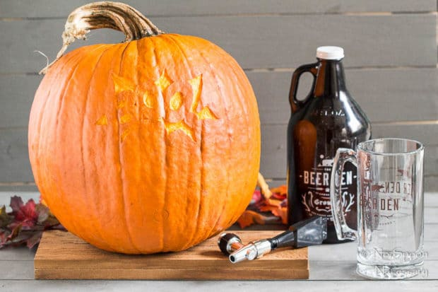 Straight on shot of all the things needed to make a pumpkin keg - a pumpkin, tap, growler of beer and beer glass.