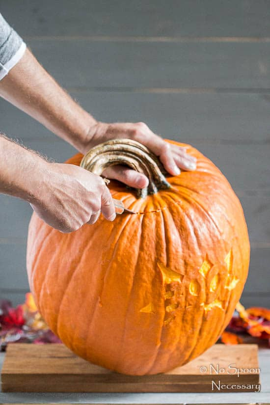 Straight on shot of a person cutting the top off of a pumpkin with a knife - photo of the second step of How To Make A Pumpkin Keg.