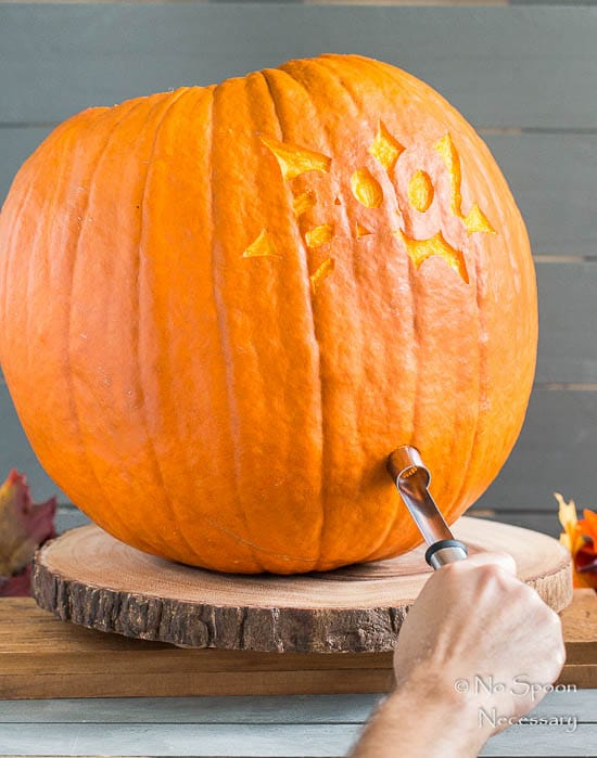 Straight on shot of a person inserting a tap into the side of a pumpkin - photo of the fourth step of How To Make A Pumpkin Keg.