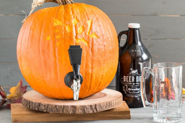 Straight on shot of a fully tapped pumpkin with a growler of beer and beer glass next to the pumpkin - photo of the fifth step of How To Make A Pumpkin Keg.