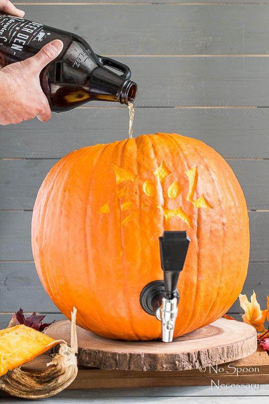 Straight on shot of a person pouring a growler of beer into a pumpkin keg - photo of the sixth step of How To Make A Pumpkin Keg.