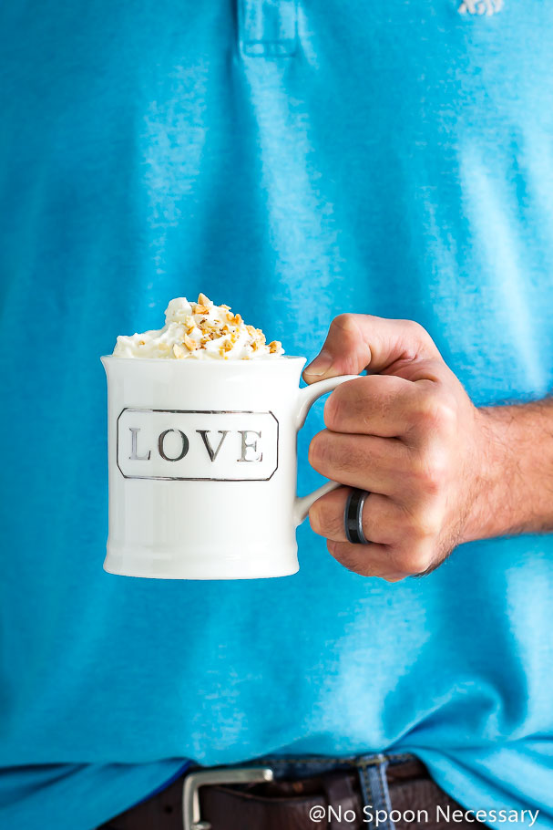 Straight on, cropped shot of a person holding a white coffee mug containing a Snickers Lava Mug Cake topped with whipped cream and chopped peanuts