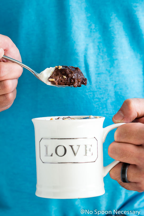 Straight on shot of a person holding a Snickers Lava Mug cake in a white coffee mug in one hand with a spoonful of the cake in the other