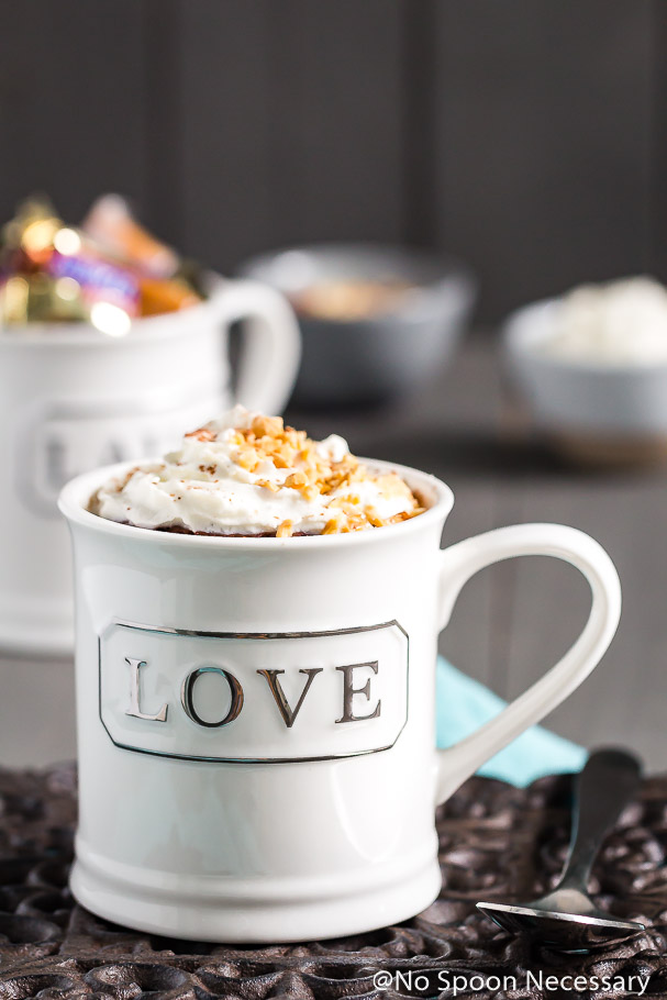 Snickers Lava Mug Cake topped with whipped cream and crushed peanuts in a white mug with the word 'love' written on it; with a mug filled with snickers candy and small bowls of whipped cream and peanuts in the background.