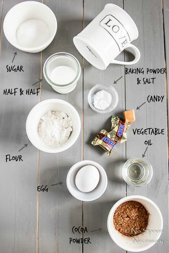 All the ingredients to make a Snickers Lava Mug Cake displayed on a gray wood board with the ingredient name written out and pointing to each individual ingredient