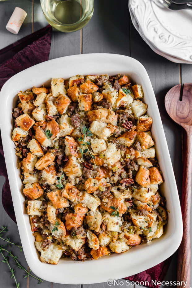 Overhead shot of Caramelized Onion, Sausage, Pecan & Croissant Stuffing in a baking dish with fresh thyme, a serving spoon, plates and glass of wine surrounding the dish.