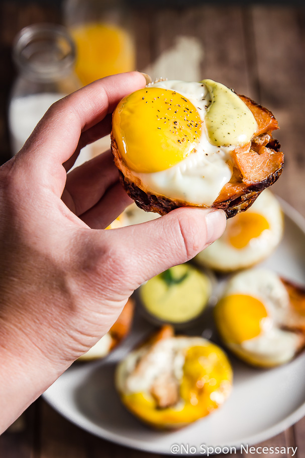45 degree angle shot of a persons hand holding a Turkey, Egg & Stuffing Muffin drizzled with blender sage hollandaise in the air with a plate of muffins blurred beneath the hand