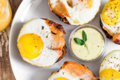Overhead shot of a Turkey, Egg & Stuffing Muffin on a white plate with a small, clear bowl of blender sage hollandaise sauce and other muffins slightly out of frame