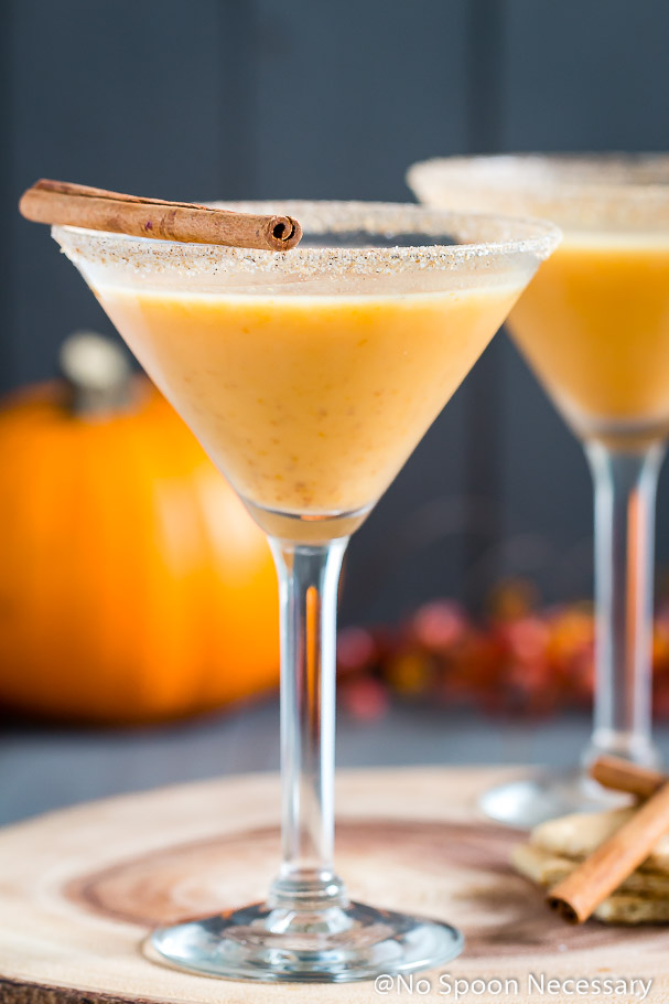 Straight on shot of a Pumpkin Pie Martini garnished with a cinnamon stick and graham cracker-sugar rim with an additional cocktail, cinnamon sticks, graham crackers, a small pumpkin and autumn decor blurred in the background.
