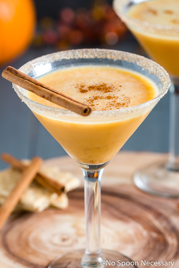 Angled shot of a Pumpkin Pie Martini garnished with a cinnamon stick and graham cracker-sugar rim with cinnamon sticks, graham crackers, a small pumpkin and autumn decor blurred in the background.