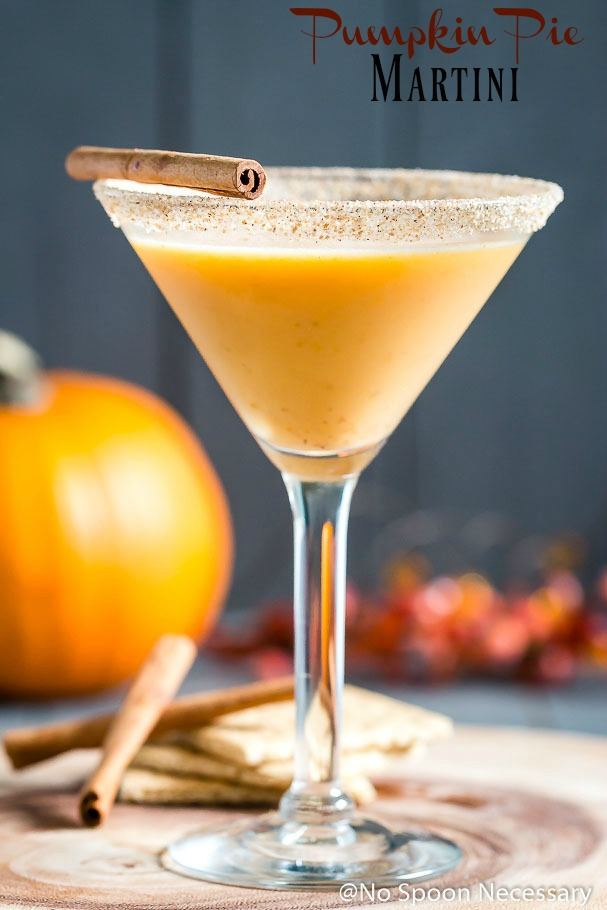 Straight on shot of a Pumpkin Pie Martini garnished with a cinnamon stick and graham cracker-sugar rim with cinnamon sticks, graham crackers, a small pumpkin and autumn decor blurred in the background.