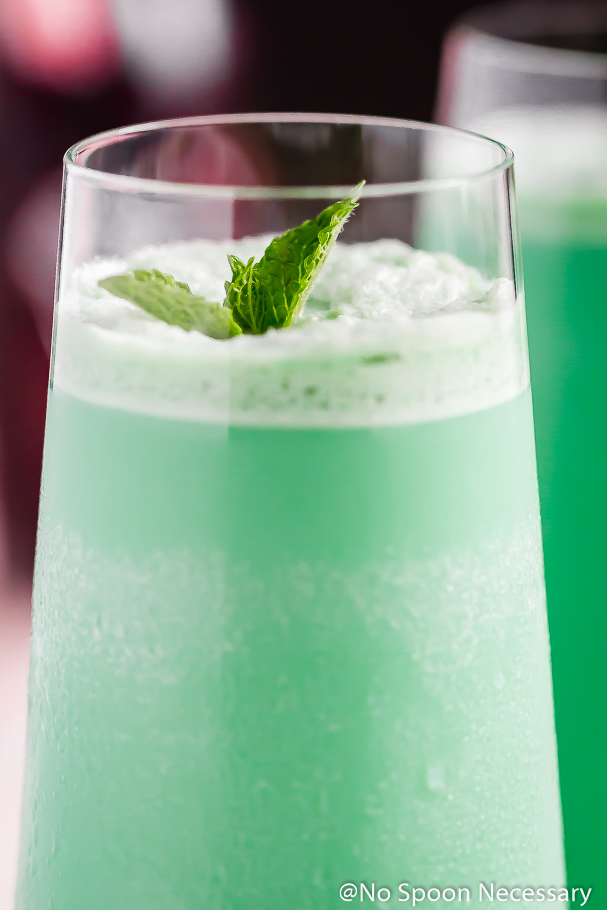 Straight on, up-close shot of the top of a Peppermint Holiday Hustler Cocktail garnished with a fresh mint sprig.