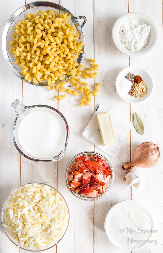 All the ingredients needed to make Lobster Macaroni n' Cheese neatly organized on a white surface