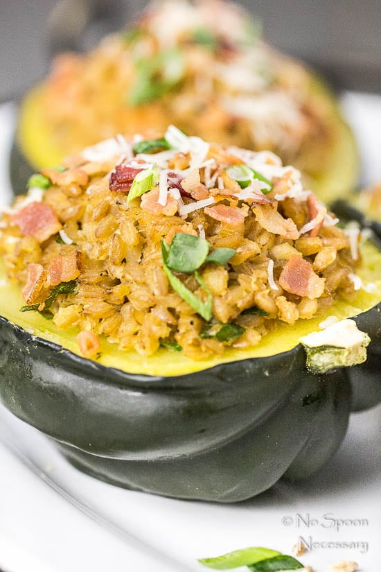 Straight on, up close shot of Bacon Scallion Farro Stuffed Acorn Squash garnished with sliced scallions and parmesan cheese on a white platter with another stuffed squash blurred in the background.