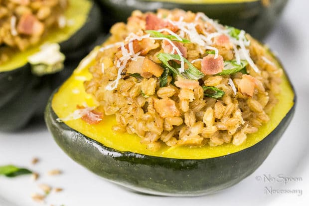 Straight on, landscape of Bacon Scallion Farro Stuffed Acorn Squash garnished with sliced scallions and parmesan cheese on a white platter with other stuffed squash blurred in the background.