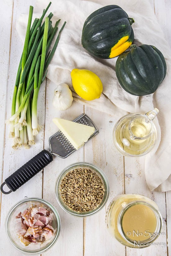 Overhead shot of all the ingredients needed to make Bacon Scallion Farro Stuffed Acorn Squash recipe neatly organized on a white wood surface.