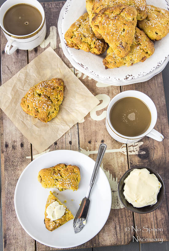 Overhead shot of a serving tray topped with an array of Bacon Butternut Squash Scones, cups of coffee and a ramekin of honey butter.