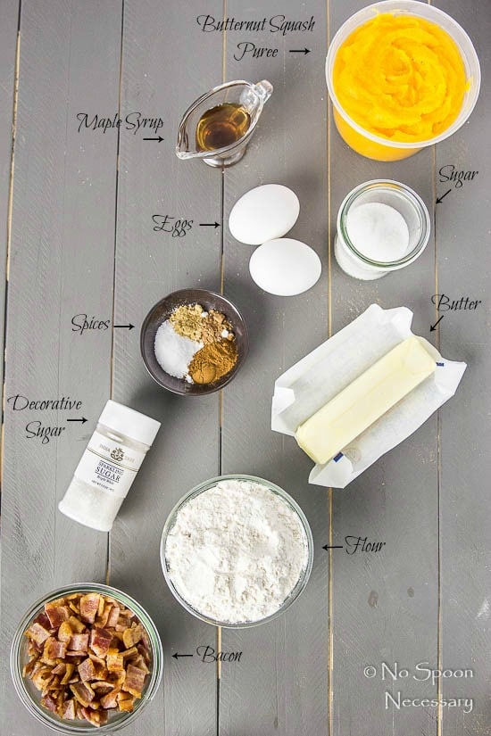 Overhead shot of all the ingredients needed to make Bacon Butternut Squash Scones recipe neatly organized on a gray wood surface with the name of each individual ingredient pointing to the ingredient.