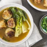 Overheat shot of a bowl of Ginger Chicken Meatball Miso Soup and Bok choy with a ramekin of sliced scallions, neutral linen and additional bowl of soup off to the side.