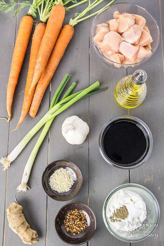 Overhead shot of all the ingredients needed to make Honey Garlic Ginger Chicken Carrot Noodle Bowls neatly organized on a gray surface.