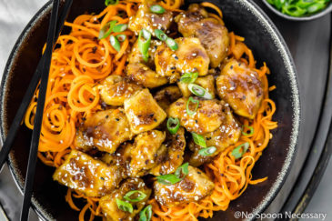 Overhead, landscape shot of Honey Ginger Garlic Chicken Carrot Noodle Bowls garnished with sliced scallions in a black bowl with black chopsticks resting on the bowl.