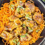 Overhead, landscape shot of Honey Ginger Garlic Chicken Carrot Noodle Bowls garnished with sliced scallions in a black bowl with black chopsticks resting on the bowl.
