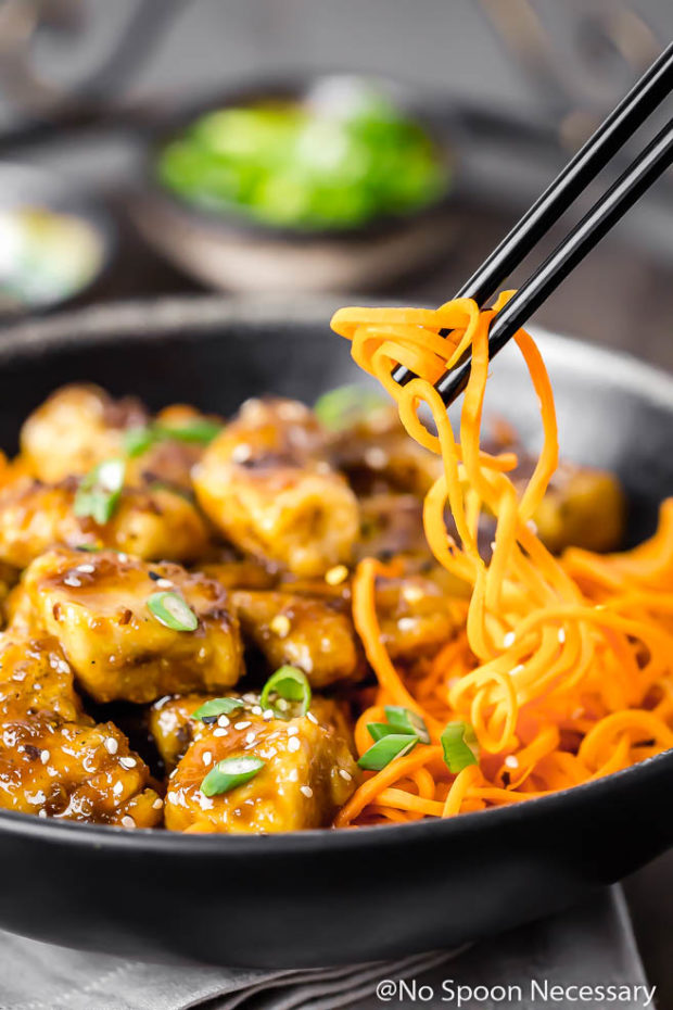 Angled shot of Honey Ginger Garlic Chicken Carrot Noodle Bowls garnished with sliced scallions in a black bowl with black chopsticks picking up the carrot noodles out of the bowl.