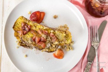 Overhead shot of a stack of Strawberry Baked Challah French Toast on a white plate with homemade strawberry maple syrup and a jar of syrup, fork, knife and pink linen to the side of the plate.