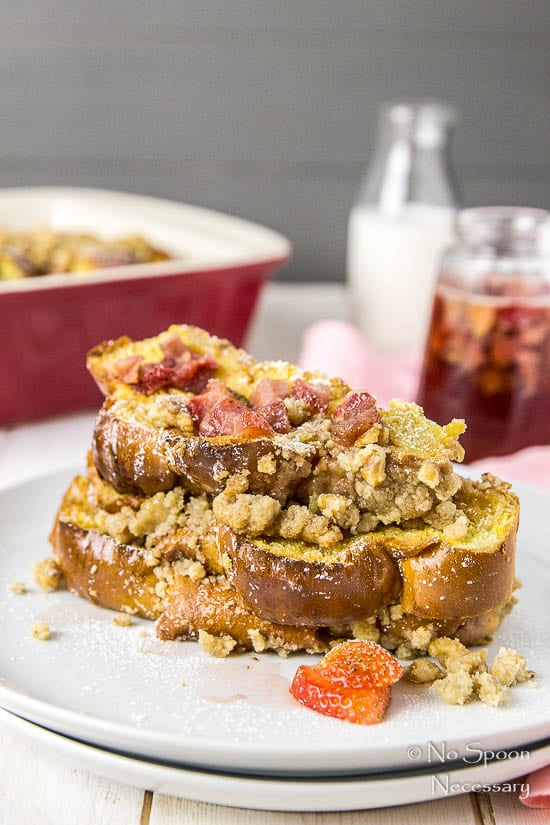 Straight on shot of a stack of Strawberry Baked Challah French Toast on a white plate with homemade strawberry maple syrup, jar of milk and french toast casserole dish blurred in the background.