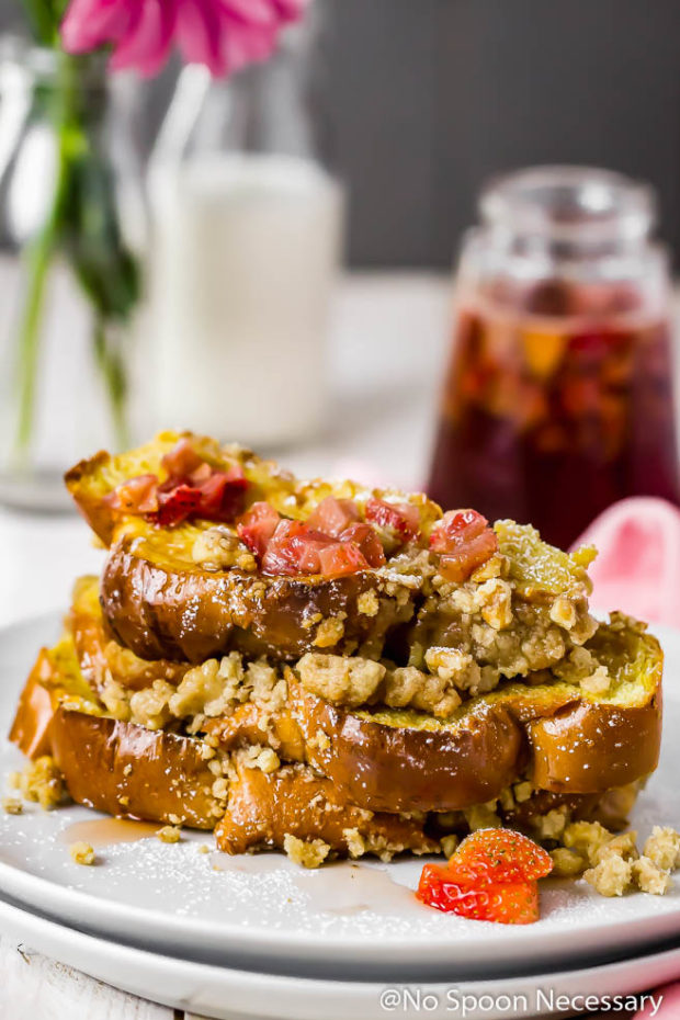 Straight on shot of a stack of Strawberry Baked Challah French Toast on a white plate with homemade strawberry maple syrup, small vase of pink flowers and a milk glass blurred in the background.
