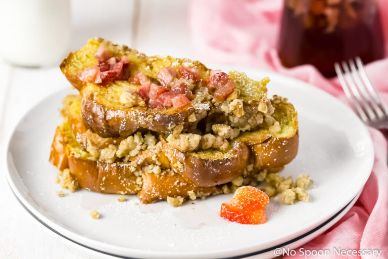 Straight on shot of a stack of Baked Strawberry French Toast on a white plate with homemade strawberry maple syrup and a jar of syrup, fork, knife and pink linen to the side of the plate.