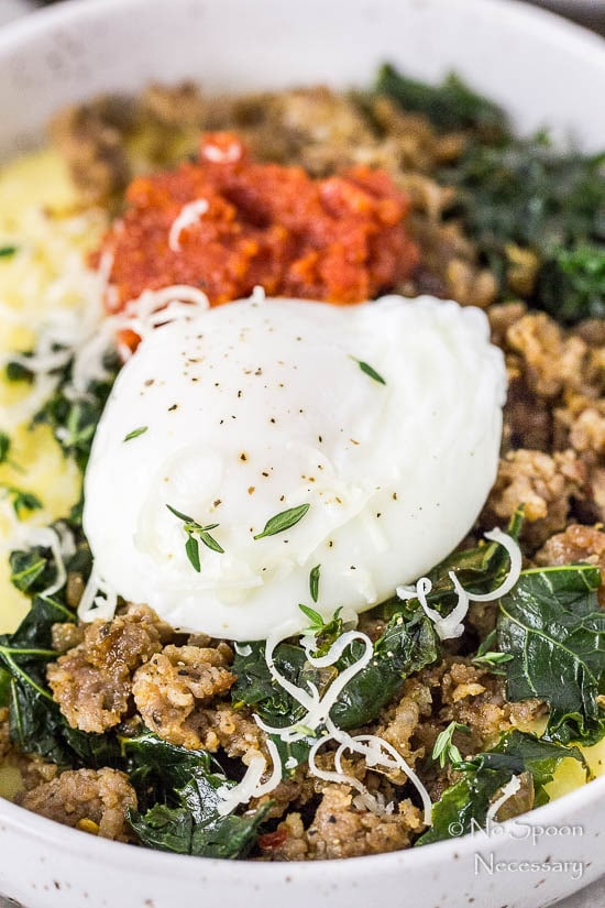 45 degree angle, up-close shot of a Sausage Breakfast Polenta Bowls with kale, sausage, poached egg and sundried tomato pesto with the focus on the poached egg.