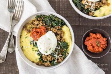 Overhead shot of two Sausage Breakfast Polenta Bowls with kale, sausage, poached egg and sundried tomato pesto on a dark wood surface and neutral linen with a stack of forks and small bowl of sun-dried tomato pesto arranged around the bowls.