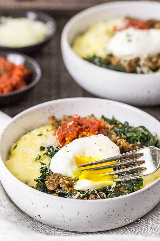 45 degree angle shot of a fork breaking the poached egg on a Sausage Breakfast Polenta Bowls with kale, sausage and sundried tomato pesto with another breakfast bowl, and small bowls of pesto and shredded cheese blurred in the background.