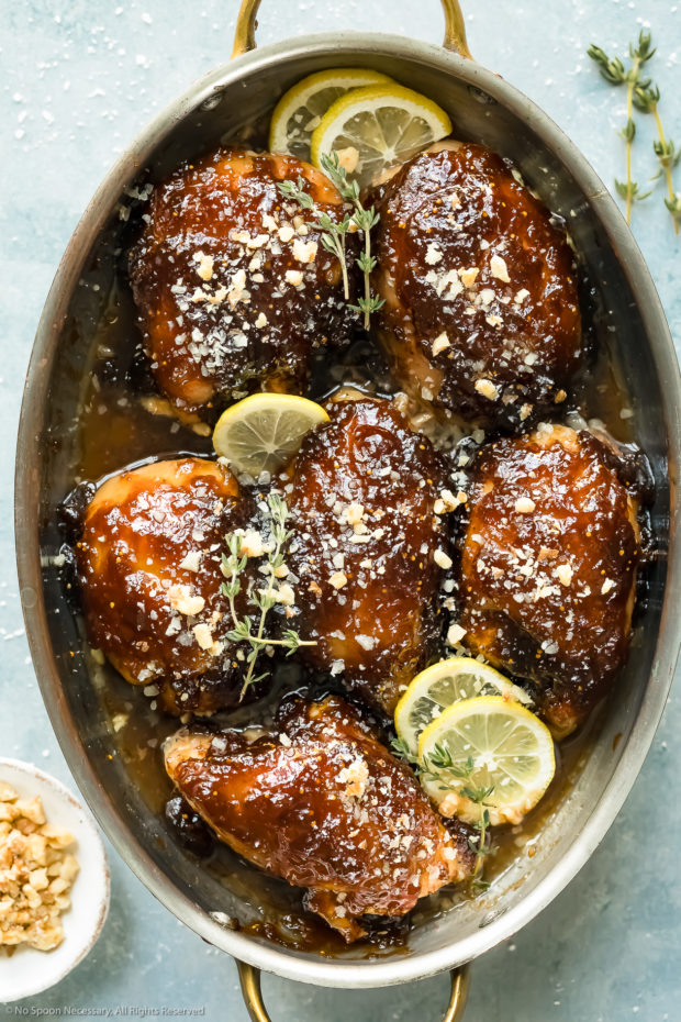 Overhead photo of Balsamic Fig Glazed Chicken garnished with lemon slices and fresh thyme in a round baking dish with a ramekin of chopped walnuts next to the dish.
